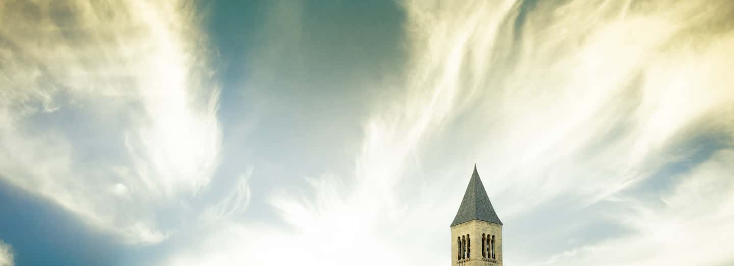 The very top of McGraw tower against a cloud-filled blue sky